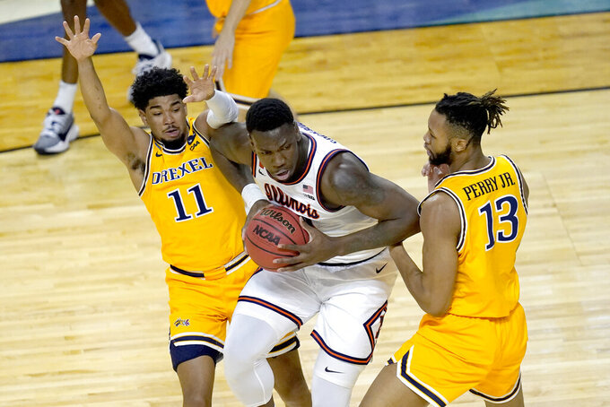 Illinois 's Kofi Cockburn, center, is pressured by Drexel's Camren Wynter (11) and Tim Perry Jr., during the first half of a first round NCAA college basketball tournament game Friday, March 19, 2021, at the Indiana Farmers Coliseum in Indianapolis .(AP Photo/Charles Rex Arbogast)