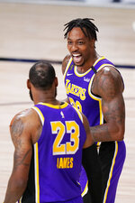 Los Angeles Lakers' Dwight Howard, right, celebrates with LeBron James (23) in the final moments of an NBA conference final playoff basketball game against the Denver Nuggets Saturday, Sept. 26, 2020, in Lake Buena Vista, Fla. The Lakers won 117-107 to win the series 4-1. (AP Photo/Mark J. Terrill)