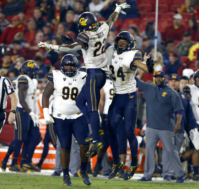 California cornerback Traveon Beck (22) celebrates his interception with cornerback Camryn Bynum (24), with nose tackle Chris Palmer (98) watching during the second half of an NCAA college football game against Southern California in Los Angeles, Saturday, Nov. 10, 2018. California won 15-14. (AP Photo/Alex Gallardo)