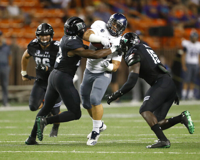Nevada running back Toa Taua (35) gets pulled down by Hawaii defensive back Ikem Okeke (22) and linebacker Paul Scott (15) during the second quarter of an NCAA college football game, Saturday, Oct. 20, 2018, in Honolulu. (AP Photo/Marco Garcia)