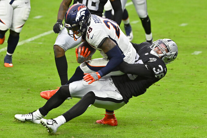 Las Vegas Raiders strong safety Jeff Heath (38) tackles Denver Broncos running back Royce Freeman (28) during the first half of an NFL football game, Sunday, Nov. 15, 2020, in Las Vegas. (AP Photo/David Becker)
