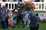 Trainer Bob Baffert attempts to get out of the way as Jockey John Velazquez tries to control Authentic in the winners' circle after winning the 146th running of the Kentucky Derby at Churchill Downs, Saturday, Sept. 5, 2020, in Louisville, Ky. (AP Photo/Jeff Roberson)