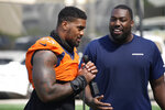 Denver Broncos defensive end Dre'Mont Jones talks to reporters as defensive end Shelby Harris looks on after an NFL football training camp at the team's headquarters Thursday, Aug. 19, 2021, in Englewood, Colo. (AP Photo/David Zalubowski)
