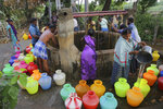 In this July 16, 2019, photo, villagers fetch water from a communal well on the outskirts of Chennai, India. In the village of Pallam just outside Chennai, some 70 families draw lots to determine when they can draw from a communal well. Normally, there is no limit on water, but now, community leaders have rationed each family to two or three pots per day, supplemented by a weekly visit by a municipal water truck that fills one plastic drum per household. (AP Photo/Manish Swarup)