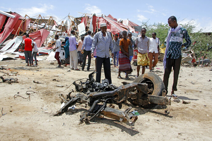 Somalis watch the wreckage of the car bomb after an attack on a European Union military convoy in the capital Mogadishu, Somalia Monday, Sept. 30, 2019. A Somali police officer says a suicide car bomber has targeted a European Union military convoy carrying Italian military trainers in the Somali capital Monday. (AP Photo/Farah Abdi Warsameh)