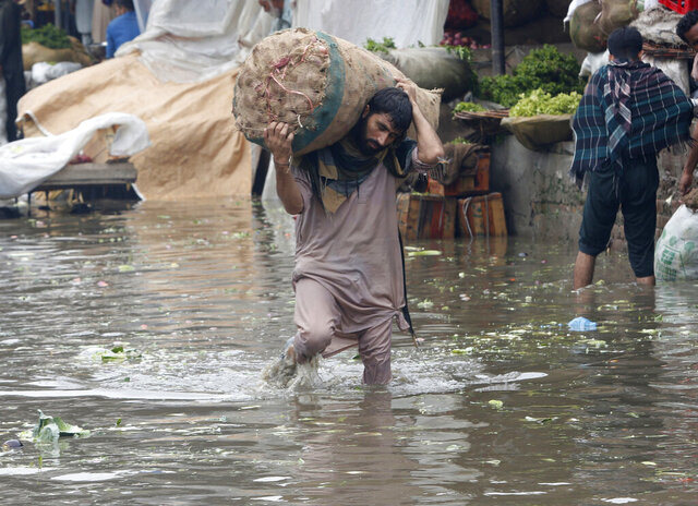 A laborer carries sack of onion while wades through a flooded area after heavy rainfall in Lahore, Pakistan, Thursday, Aug. 20, 2020. Emergency workers say relentless monsoon rains kill some people and injure many in Pakistan's most populous Punjab province. (AP Photo/K.M. Chaudary)