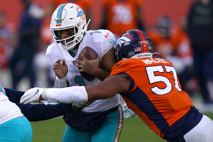 Miami Dolphins quarterback Tua Tagovailoa (1) is sacked by Denver Broncos defensive end DeMarcus Walker (57) during the first half of an NFL football game, Sunday, Nov. 22, 2020, in Denver. (AP Photo/David Zalubowski)