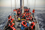 Migrants rest on a Mediterranea Saving Humans NGO boat, as they sail off Italy's southernmost island of Lampedusa, just outside Italian territorial waters, on Thursday, July 4, 2019. An Italian humanitarian group whose boat has been barred from docking in Lampedusa said the health of the 54 migrants it rescued at sea is rapidly deteriorating, prompting fears of another standoff with Italy's populist government. Mediterranea Saving Humans said Friday in a tweet that its sailing boat ALEX was off Italy's southernmost island of Lampedusa, just outside Italian territorial waters, and that it has been banned from entering Italian jurisdiction by ministerial decree. (AP Photo/Olmo Calvo)