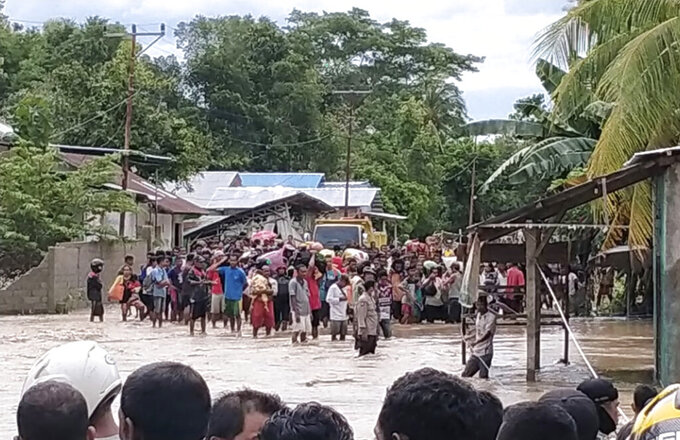Residents wait for help to cross a flooded road in Malaka Tengah, East Nusa Tenggara province, Indonesia, Monday, April 5, 2021. Multiple disasters caused by torrential rains in eastern Indonesia have left dozens of people dead and missing and displaced thousands, the country's disaster relief agency said Monday. (AP Photo)
