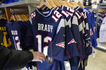 A person browses for Tom Brady jerseys in the pro shop at Gillette Stadium, Monday, Jan. 25, 2021, in Foxborough, Mass. Tom Brady is going to the Super Bowl for the 10th time, and New England Patriots football fans are cheering for him -- just like before. (AP Photo/Elise Amendola)
