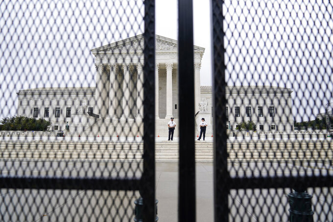 FILE - In this Sept. 17, 2021 file photo U.S. Capitol police officers walk near fencing around the Supreme Court in Washington. Twenty-five media and transparency groups are asking the Washington Supreme Court to allow the release of the names of the Seattle police officers who attended events in Washington D.C. on Jan. 6 — the day of the insurrection. The Reporters Committee for the Freedom of the Press and the news organizations are asking the court to deny an injunction filed by the officers that seeks to block the release of public records that identify the officers. (AP Photo/Brynn Anderson, file)