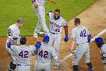New York Mets' Amed Rosario , center, runs home to score as teammates celebrate following his walkoff home run off New York Yankees relief pitcher Aroldis Chapman in the seventh inning of the second baseball game of a doubleheader, Friday, Aug. 28, 2020, in New York. All players and management staff are wearing No. 42 as a tribute to baseball great Jackie Robinson. (AP Photo/John Minchillo)