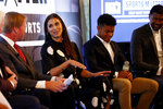 FILE - In this Thursday, July 18, 2019, file photo, Dick's Sporting Goods Chairman and CEO Edward W. Stack, obscured at far left, and Jon Gruden, second from left, talk with Alex Morgan, center, at the DICK'S Sports Matter Panel Event in New York. Second from right is Jordany Baltazar and Jalen Rose is at right. Jon Gruden, Larry Fitzgerald and Alex Morgan have reached the summit of their professions. They all recognize the need for strong grass-roots sports programs, and they are doing something about it.  Working with DICK'S Sporting Goods Foundation, that trio announced a pledge to provide access to sports for one million youngsters over the next five years. DICK'S will match up to $1 million in donations made by customers to its foundation. (Jason DeCrow/AP Images for DICK'S Sporting Goods, File)