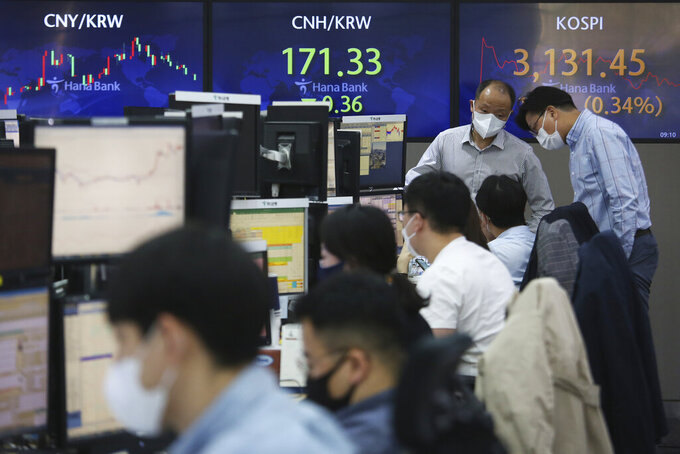 Currency traders wearing face masks work at the foreign exchange dealing room of the KEB Hana Bank headquarters in Seoul, South Korea, Tuesday, April 6, 2021. Asian shares were mixed Tuesday after a Wall Street rally that reflected some optimism about the economy recovering from the damage of the coronavirus pandemic. (AP Photo/Ahn Young-joon)