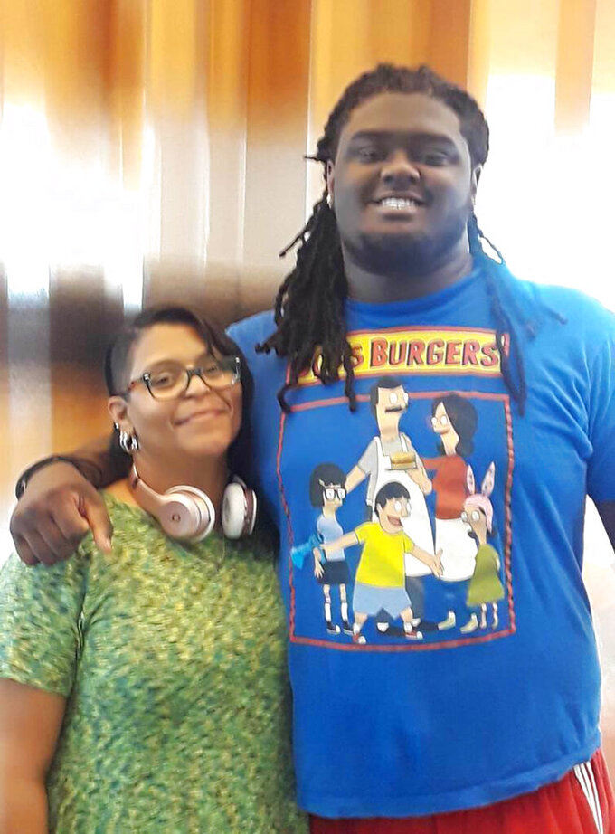 In this undated photo provided by Joanne Atkins-Ingram, Atkins-Ingram poses with her son Braeden Bradforth. Attorneys for the parents of the 19-year-old football player who died of heatstroke on the first day of practice at a Kansas community college said Thursday, Dec. 12, 2019, that negotiations with the school remain on track, downplaying the significance of Tuesday's decision by trustees to deny claims totaling $50 million. Bradforth, a 315-pound (140-kilogram) defensive lineman for Garden City Community College, was found unconscious in an alley outside his dormitory after practice on Aug. 1, 2018. The Newton, New Jersey, teenager died that night at a hospital. (Courtesy Joanne Atkins-Ingram via AP)