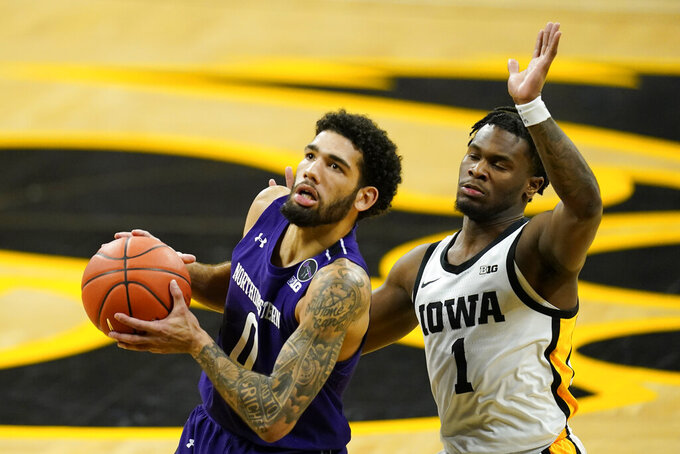 Northwestern guard Boo Buie drives to the basket past Iowa guard Joe Toussaint, right, during the first half of an NCAA college basketball game, Tuesday, Dec. 29, 2020, in Iowa City, Iowa. (AP Photo/Charlie Neibergall)