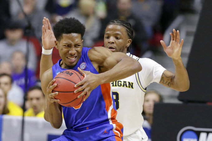 Florida's KeVaughn Allen (5) is guarded by Michigan's Zavier Simpson, right, during the first half of a second round men's college basketball game in the NCAA Tournament, in Des Moines, Iowa, Saturday, March 23, 2019. (AP Photo/Nati Harnik)