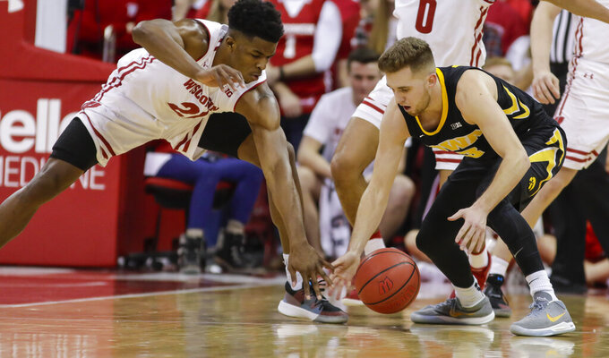Wisconsin's Khalil Iverson (21) and Iowa's Jordan Bohannon (3) go after a loose ball during the second half of an NCAA college basketball game Thursday, March 7, 2019, in Madison, Wis. Wisconsin won 65-45. (AP Photo/Andy Manis)