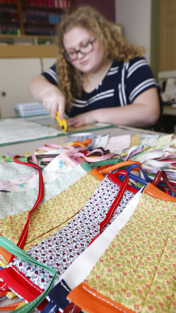 Intern Megan Murphy cuts fabric to make health masks at the Eau Claire Children's Theatre in Eau Claire, Wis., on March 24, 2020. Creating a mask involves several steps and takes ECCT employees around 20 minutes to finish. (Dan Reiland/The Eau Claire Leader-Telegram via AP)