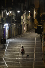 A resident walks with a dog along an empty Curia street, in Pamplona, northern Spain, Saturday, Oct. 24, 2020, as new measures against the coronavirus began in the Navarra province where all bar and restaurants are closed for 15 days from midnight Wednesday.  (AP Photo/Alvaro Barrientos)