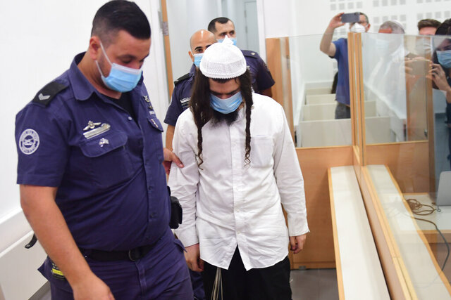 Israeli right-wing activist Amiram Ben-Uliel arrives at a district court for a verdict in the city of Lod, Israel, Monday, May 18, 2020. An Israeli district court has convicted Ben-Uliel of murder in a 2015 arson attack that killed a Palestinian toddler and his parents. (Avshalom Sassoni/Pool Photo via AP)