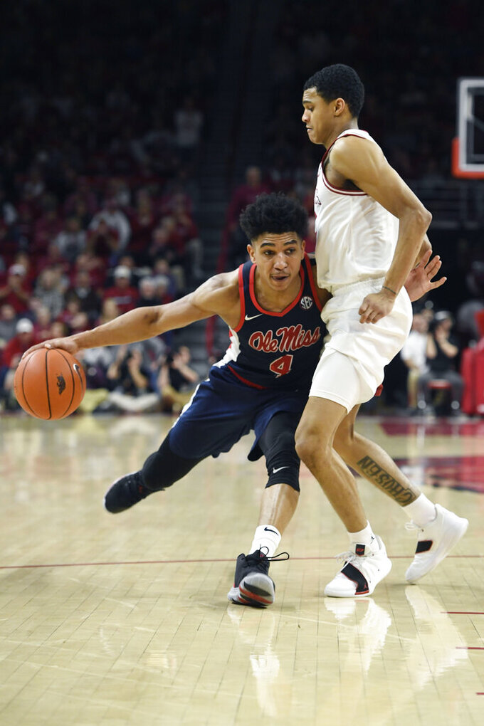 Mississippi guard Breein Tyree (4) tries to get past Arkansas defender Jalen Harris (5) during the second half of an NCAA college basketball game, Saturday, March 2, 2019 in Fayetteville, Ark. (AP Photo/Michael Woods)