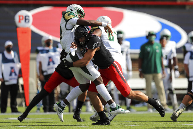 South Florida quarterback Katravis Marsh, left, throws as he is hit by Cincinnati linebacker Ty Van Fossen, right, during the first half of an NCAA college football game, Saturday, Oct. 3, 2020, in Cincinnati. (AP Photo/Aaron Doster)