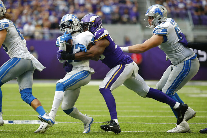 Detroit Lions running back D'Andre Swift, left, is tackled by Minnesota Vikings defensive end Danielle Hunter (99) during the second half of an NFL football game, Sunday, Oct. 10, 2021, in Minneapolis. (AP Photo/Bruce Kluckhohn)