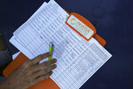 In this Feb. 19. 2019 photo, a clipboard shows the names of the persons who signed up to volunteer to help bring humanitarian, during a meeting to recruit volunteers, at a square in Caracas, Venezuela. So far, more than 800,000 volunteers have signed up to help through a designated website, organizers say. (AP Photo/Fernando Llano)