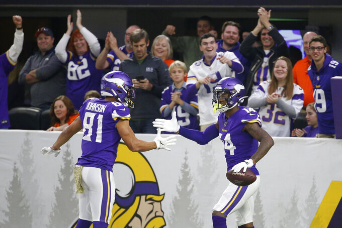 Minnesota Vikings wide receiver Stefon Diggs, right, celebrates with teammate Bisi Johnson, left, after catching a 54-yard touchdown pass during the second half of an NFL football game against the Denver Broncos, Sunday, Nov. 17, 2019, in Minneapolis. (AP Photo/Bruce Kluckhohn)