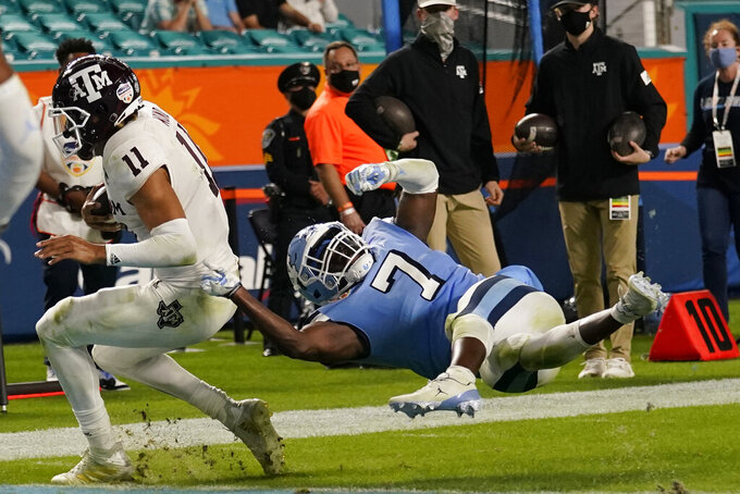 North Carolina linebacker Eugene Asante (7) attempts to stop Texas A&M quarterback Kellen Mond (11) as he runs for a touchdown during the second half of the Orange Bowl NCAA college football game, Saturday, Jan. 2, 2021, in Miami Gardens, Fla. (AP Photo/Lynne Sladky)