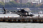 In this Wednesday, Oct. 2, 2019, photo passengers exit an Uber helicopter at the Downtown Manhattan Heliport, in New York. The ride-hailing company expanded its helicopter service Thursday, Oct. 3, between lower Manhattan in New York City and John F. Kennedy International Airport, making it available to all Uber riders with iPhones instead of just those in the top tiers of its rewards program. Uber hopes to deploy it to Android users soon. (AP Photo/Richard Drew)