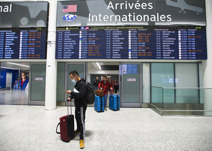 A man wears a masks following the outbreak of a new virus as people arrive from the International terminal at Toronto Pearson International Airport in Toronto on Saturday, Jan. 25, 2020. A Toronto hospital said Saturday it has a confirmed case of the deadly virus from China, Canada's first. Sunnybrook Health Sciences Centre said it is