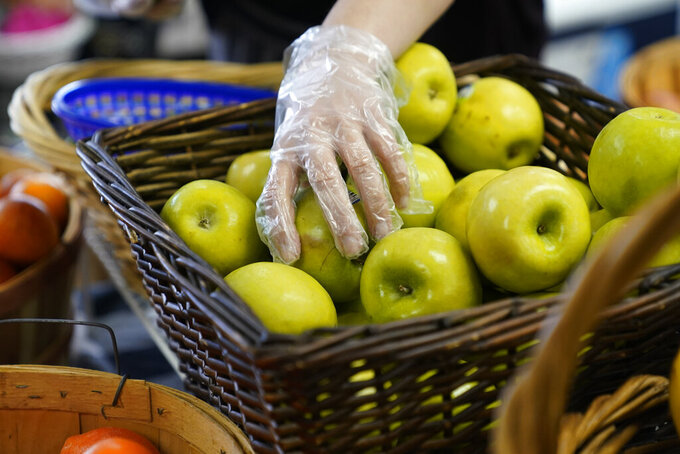 Alex Miller takes an apple at Porchlight Community Service food pantry Thursday, May 6, 2021, in San Diego. For millions of Americans with food allergies or intolerances, the pandemic has created a particular crisis: Most food banks and government programs offer limited options. (AP Photo/Gregory Bull)