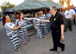 FILE - In this Saturday, June 23, 2012, file photo, Maricopa County Sheriff Joe Arpaio signs autographs for inmates as he walks through a Maricopa County Sheriff's Office jail called