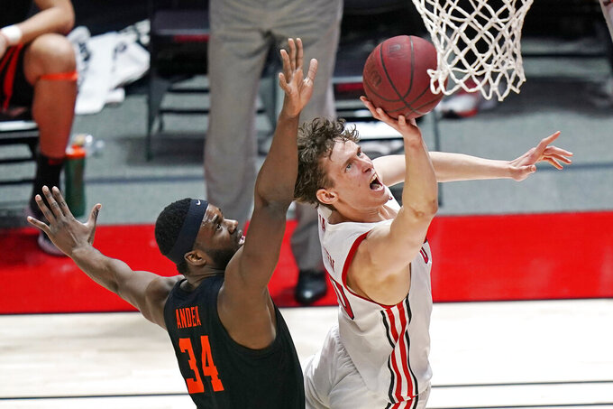 Utah forward Mikael Jantunen (20) goes to the basket as Oregon State forward Rodrigue Andela (34) defends during the first half of an NCAA college basketball game Wednesday, March 3, 2021, in Salt Lake City. (AP Photo/Rick Bowmer)