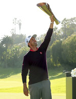 Adam Scott, of Australia, hoists his trophy on the 18th green after winning the Genesis Invitational golf tournament at Riviera Country Club, Sunday, Feb. 16, 2020, in the Pacific Palisades area of Los Angeles. (AP Photo/Ryan Kang)