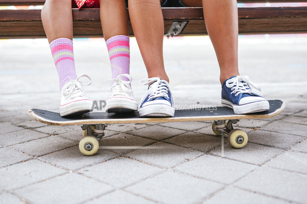 Friends with skateboard sitting on bench
