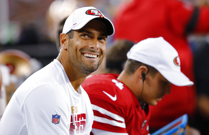 San Francisco 49ers quarterback Jimmy Garoppolo, left, smiles on the bench next to quarterback Nick Mullens during the second half of the team's NFL preseason football game against the Dallas Cowboys in Santa Clara, Calif., Saturday, Aug. 10, 2019. (AP Photo/John Hefti)