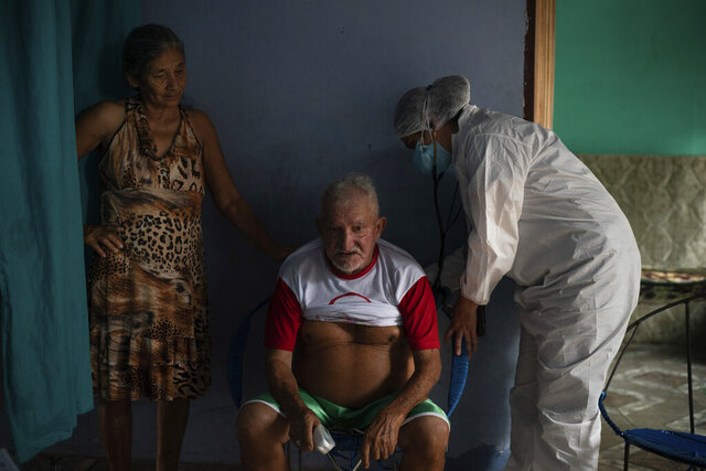Francisco de Oliveira, 77, takes a deep breath while Doctor Dayanne Araujo listens to his lungs in Manacapuru, Amazonas state, Brazil, Tuesday, June 2, 2020. Oliveira is waiting for his COVID-19 test results after feeling weakness, difficulty breathing and other symptoms. (AP Photo/Felipe Dana)