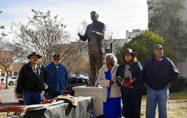 Vernon Dahmer's widow, Ellie Dahmer, center, and some of the late civil rights leader's children pose for a picture at the installment of Vernon Dahmer's sculpture, Tuesday, Dec. 3, 2019, at Forrest County Courthouse in Hattiesburg, Miss. (Lici Beveridge/Hattiesburg American via AP)