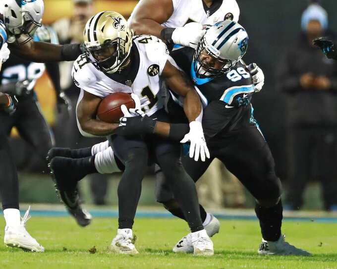 FILE - In this Dec. 17, 2018, file photo, New Orleans Saints' Alvin Kamara (41) is tackled by Carolina Panthers' Kawann Short (99) in the first half of an NFL football game in Charlotte, N.C. Panthers two-time Pro Bowler Short thought about opting out of the NFL season, but the 6-foot-3, 315-pound defensive tackle simply could not bear the thought of missing another football season. (AP Photo/Jason E. Miczek, File)