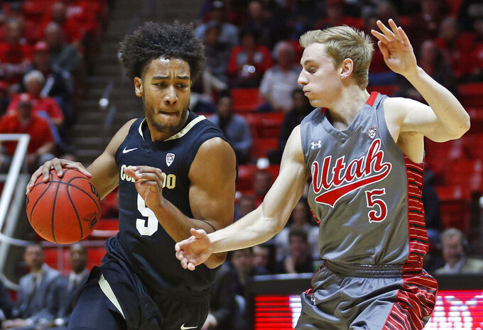 Colorado guard D'Shawn Schwartz, left, drives around Utah guard Parker Van Dyke (5) during the first half of an NCAA college basketball game Sunday, Jan. 20, 2019, in Salt lake City. (AP Photo/Rick Bowmer)