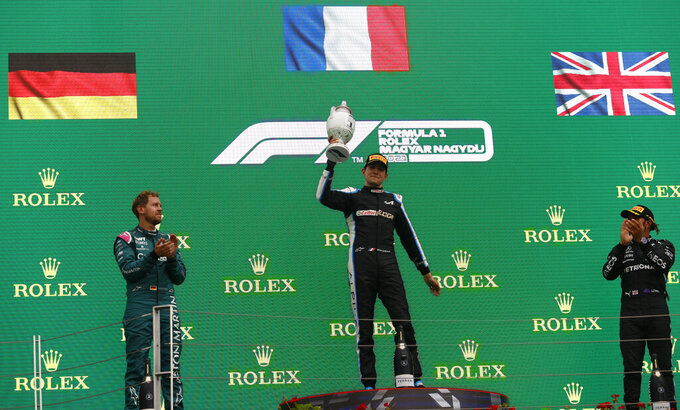Race winner, Alpine driver Esteban Ocon of France, center, celebrates on the podium with second placed Aston Martin driver Sebastian Vettel of Germany, left, and third placed Mercedes driver Lewis Hamilton of Britain after the Hungarian Formula One Grand Prix, at the Hungaroring racetrack in Mogyorod, Hungary, Sunday, Aug. 1, 2021. (Florion Goga/Pool via AP)