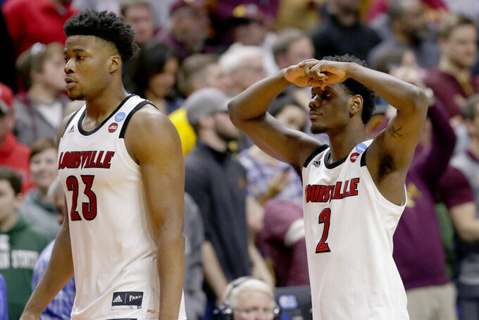Louisville's Darius Perry (2) and Steven Enoch (23) walk off the court following their 86-76 loss to Minnesota in a first round men's college basketball game in the NCAA Tournament, in Des Moines, Iowa, Thursday, March 21, 2019.  (AP Photo/Nati Harnik)