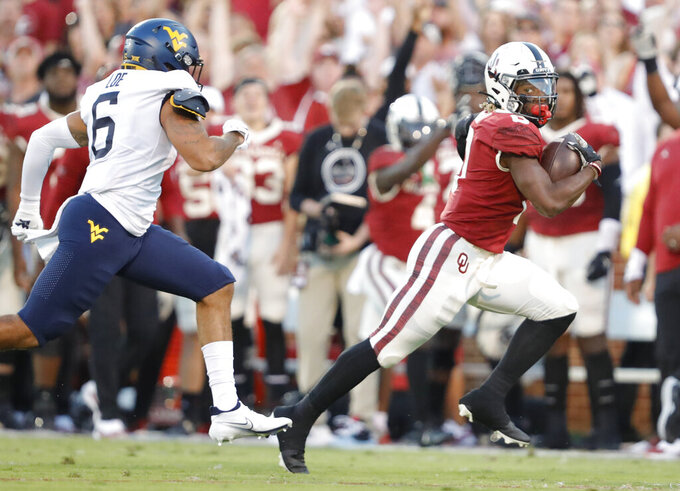 Oklahoma running back Eric Gray (0) runs ahead of West Virginia linebacker Exree Loe (6) for a first down during the first half of an NCAA college football game in Norman, Okla., Saturday, Sep. 25, 2021. (AP Photo/Alonzo Adams)