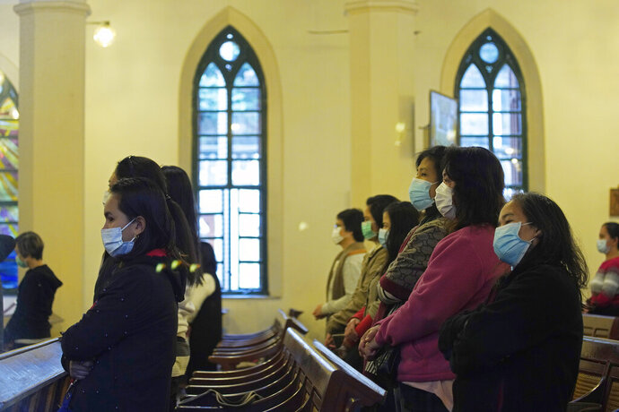 In this Feb. 9, 2020, photo, church goers wearing face masks attend a mass at the St John's Cathedral in Hong Kong. People who troop to churches and chapels were asked to wear protective masks and keep some distance to each other in Hong Kong. (AP Photo/Vincent Yu)