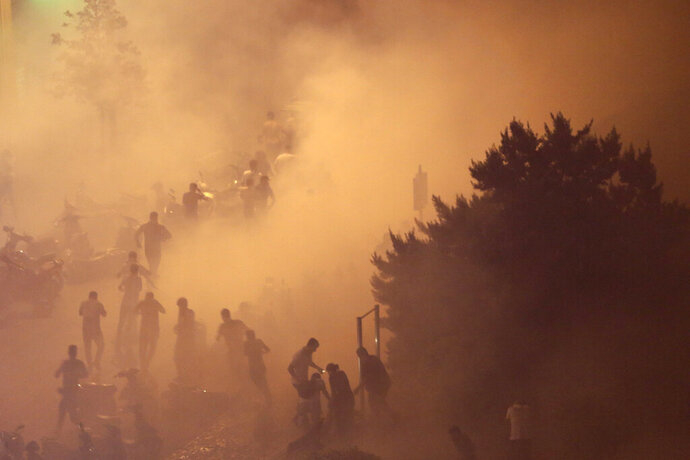 Lebanese riot police fire tear gas during a protest against government's plans to impose new taxes in Beirut, Lebanon, Friday, Oct. 18, 2019. Lebanon erupted in protests Thursday over the government's plans to impose new taxes amid a severe economic crisis, taking their anger on politicians they accuse of widespread corruption and decades of mismanagement. (AP Photo/Hassan Ammar)