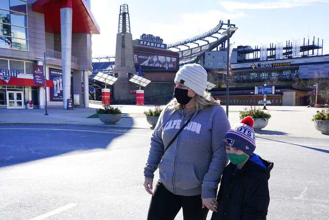 Kelly Roccabello and her son, Giovanni, 6, walk outside the pro shop at Gillette Stadium, Monday Jan. 25, 2021, in Foxborough, Mass. Tom Brady is going to the Super Bowl for the 10th time, and New England Patriots football fans are cheering for him -- just like before. (AP Photo/Elise Amendola)