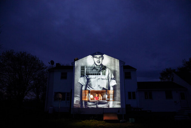 An image of veteran Charles Lowell is projected onto the home he shared with his wife, Alice, for 30 years as she stands at left with her daughter, Susan Kenney, in Hardwick, Mass. Saturday, May 2, 2020. Lowell, a U.S. Air Force veteran and resident of the Soldier's Home in Holyoke, Mass., died from the COVID-19 virus at the age of 78. Seeking to capture moments of private mourning at a time of global isolation, the photographer used a projector to cast large images of veterans on to the homes as their loved ones are struggling to honor them during a lockdown that has sidelined many funeral traditions. (AP Photo/David Goldman)